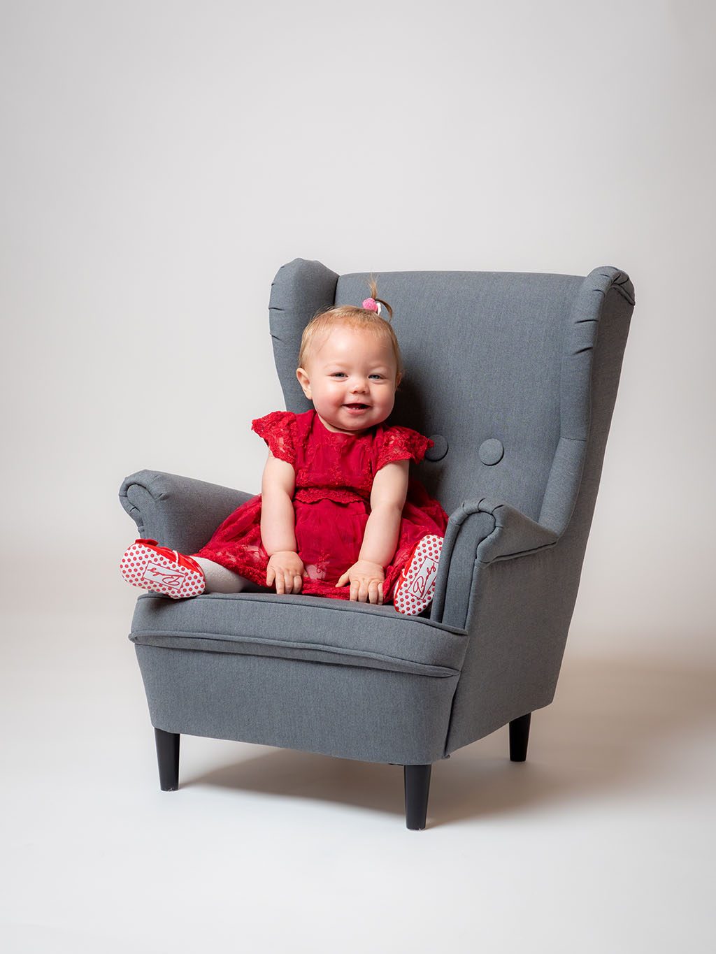 baby smiling sitting up in chair for photos taken by qualified baby photographer in Braintree, Essex