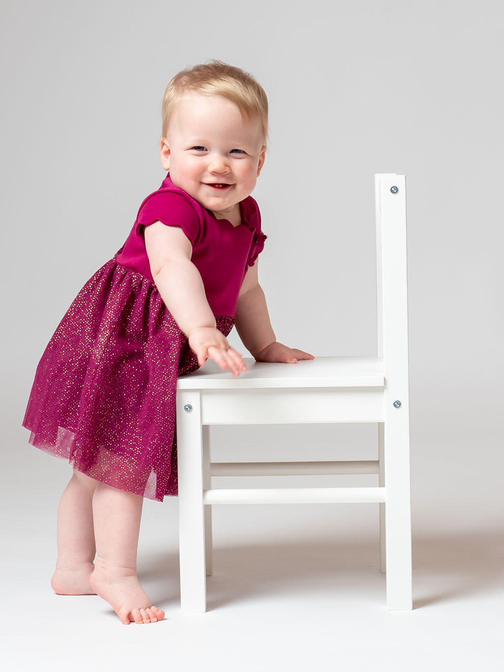 little baby toddler just standing holding on to white chair for support while smiling taken by qualified baby photographer in Braintree, Essex