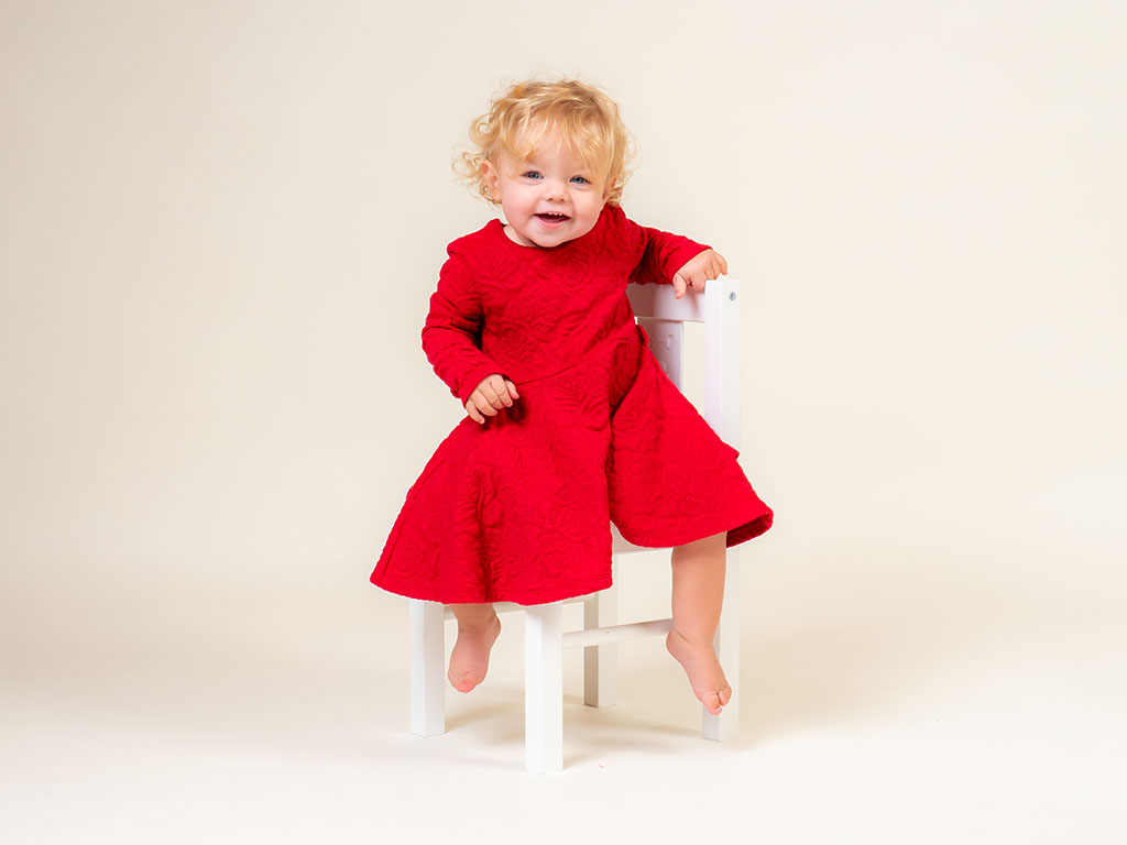 baby girl in red dress smiling and resting arm on chair taken by qualified baby photographer in Braintree, Essex