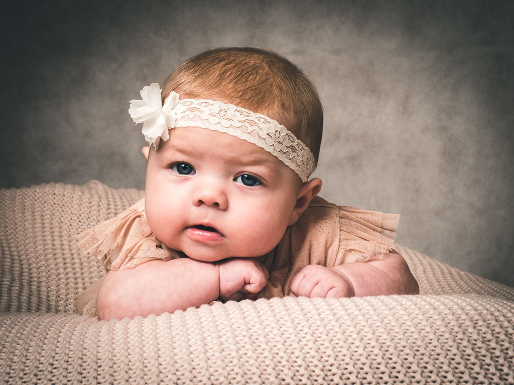 baby on beanbag looking at you while wearing a pretty headband taken by qualified baby photographer in Braintree, Essex