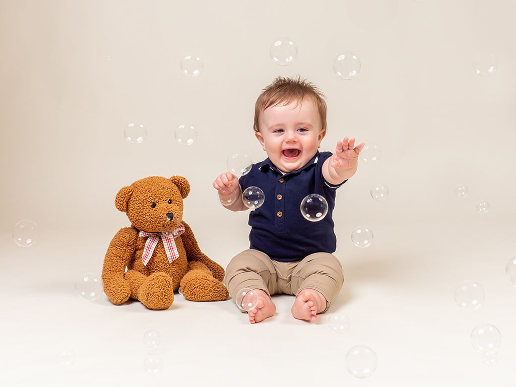 baby reaching stretching for bubbles sitting on floor next to teddy taken by qualified baby photographer in Braintree, Essex