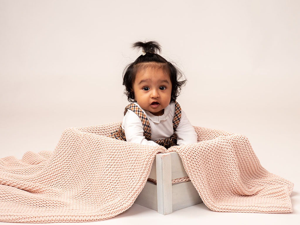 baby sitting up in box looking at you taken by qualified baby photographer in Braintree, Essex
