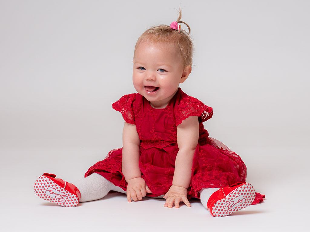 baby sitting up on her own smiling while sitting on the floor taken by qualified baby photographer in Braintree, Essex