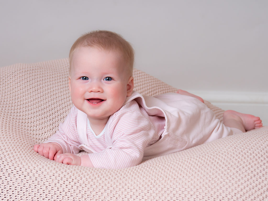 beautiful baby girl on her tummy smiling for the camera posing taken by qualified baby photographer in Braintree, Essex