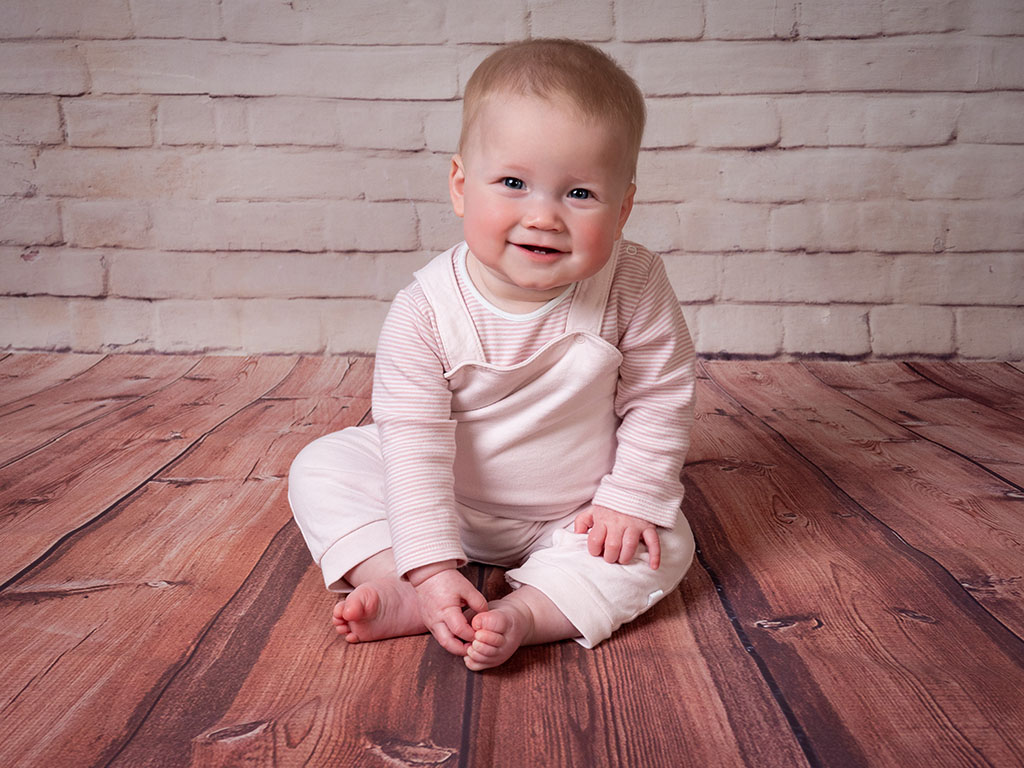 cute baby sitting unaided while touching her tiny toes and smiling taken by qualified baby photographer in Braintree, Essex