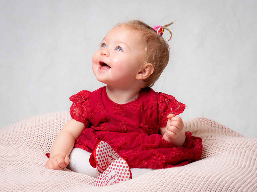 pretty baby sitting on own unaided smiling at the light wearing a red dress taken by qualified baby photographer in Braintree, Essex