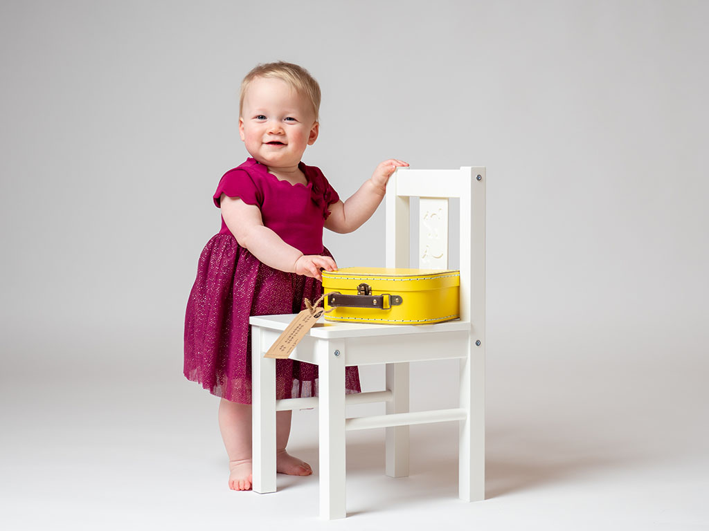 pretty baby standing with support holidng on to while wooden chair and bright yellow suitcase taken by qualified baby photographer in Braintree, Essex