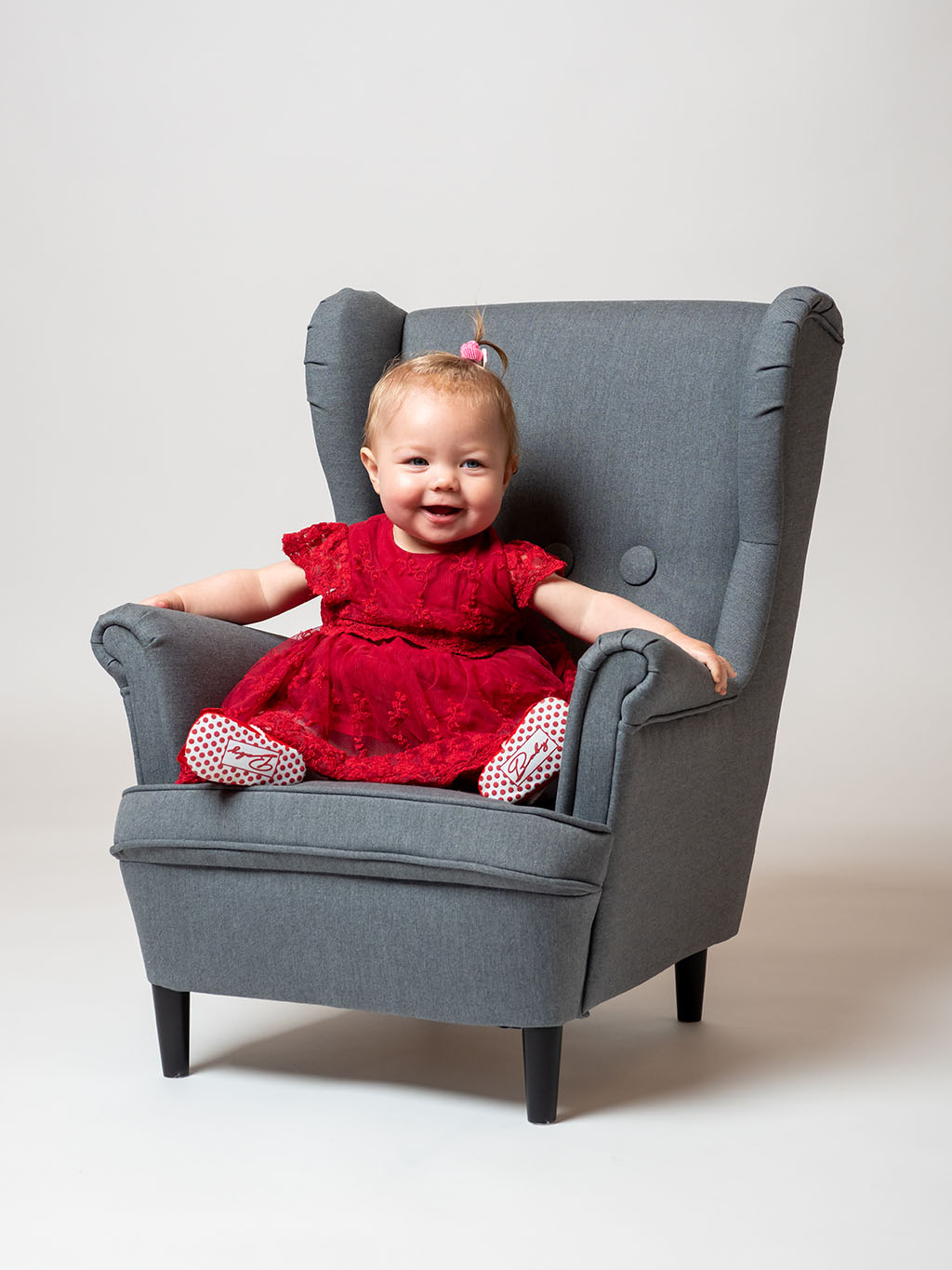 smiling baby sitting in armchair in the studio taken by qualified baby photographer in Braintree, Essex
