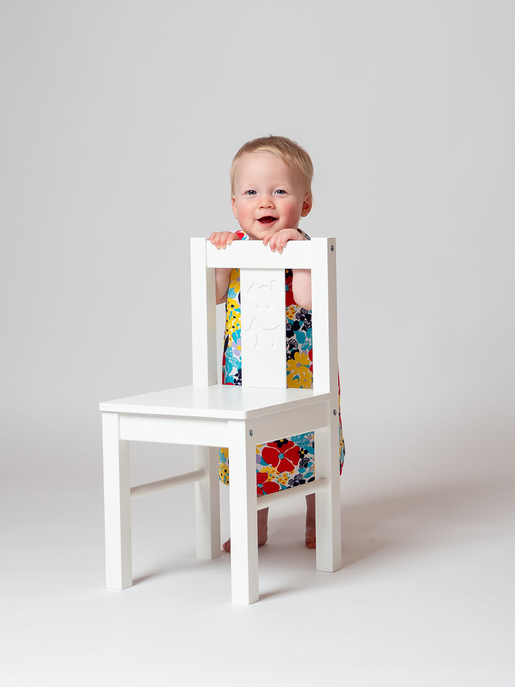 tiny toddler standing behind white wooden chair smiling at the camera taken by qualified baby photographer in Braintree, Essex