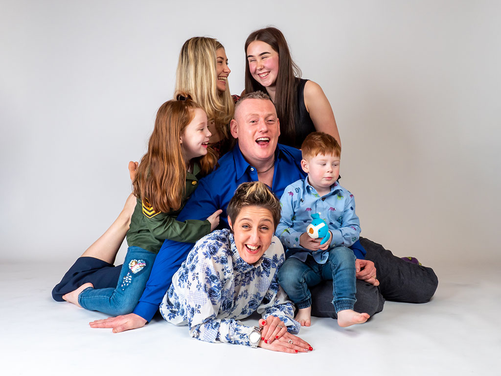 Mum and dad with 4 children laughing and having fun in photography studio