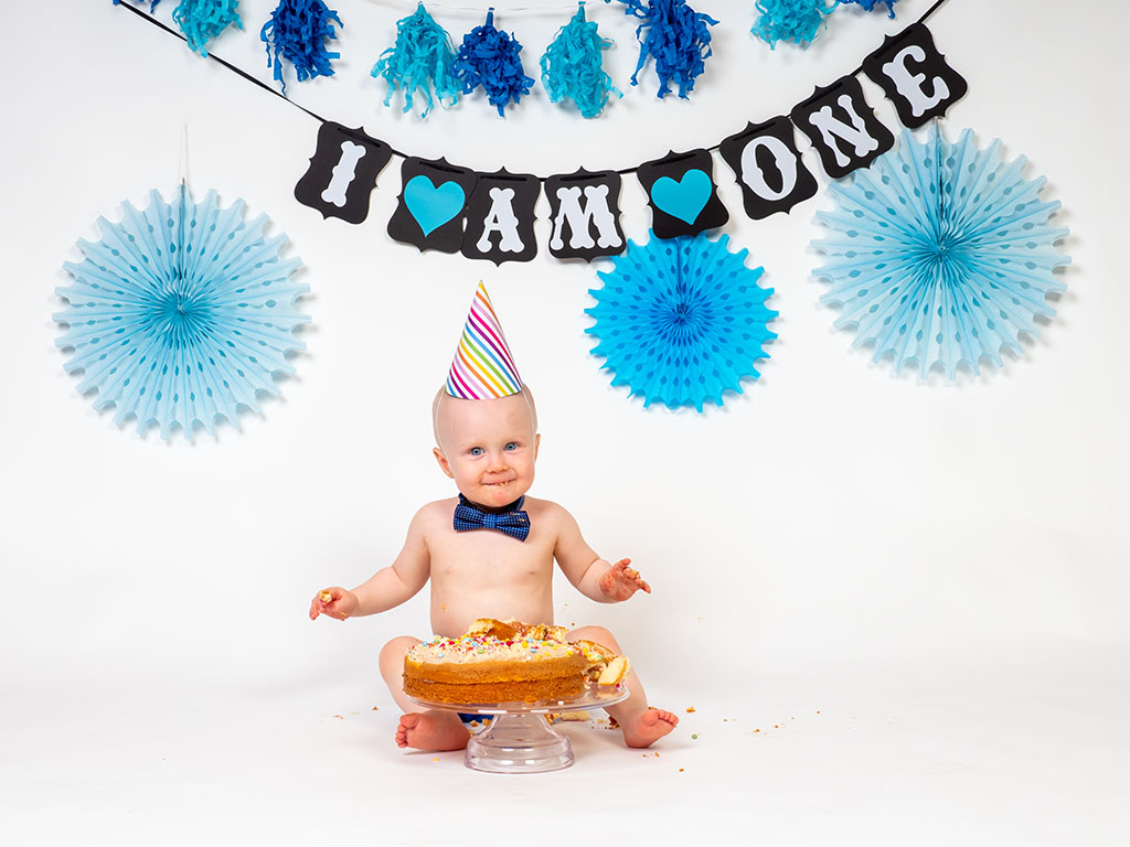 baby boy sitting with cake smashed on cake stand taken by cake smash photographer in Braintree