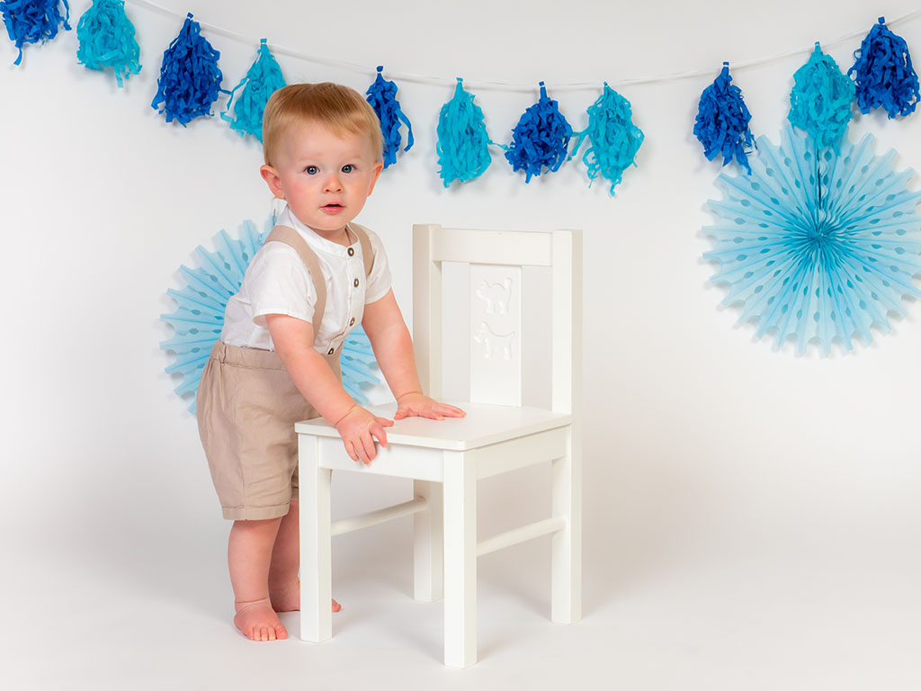 baby boy standing by white chair before cake smash taken by baby photographer in Braintree