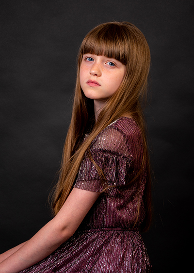 Young girl with long hair sitting side on to camera with serious face