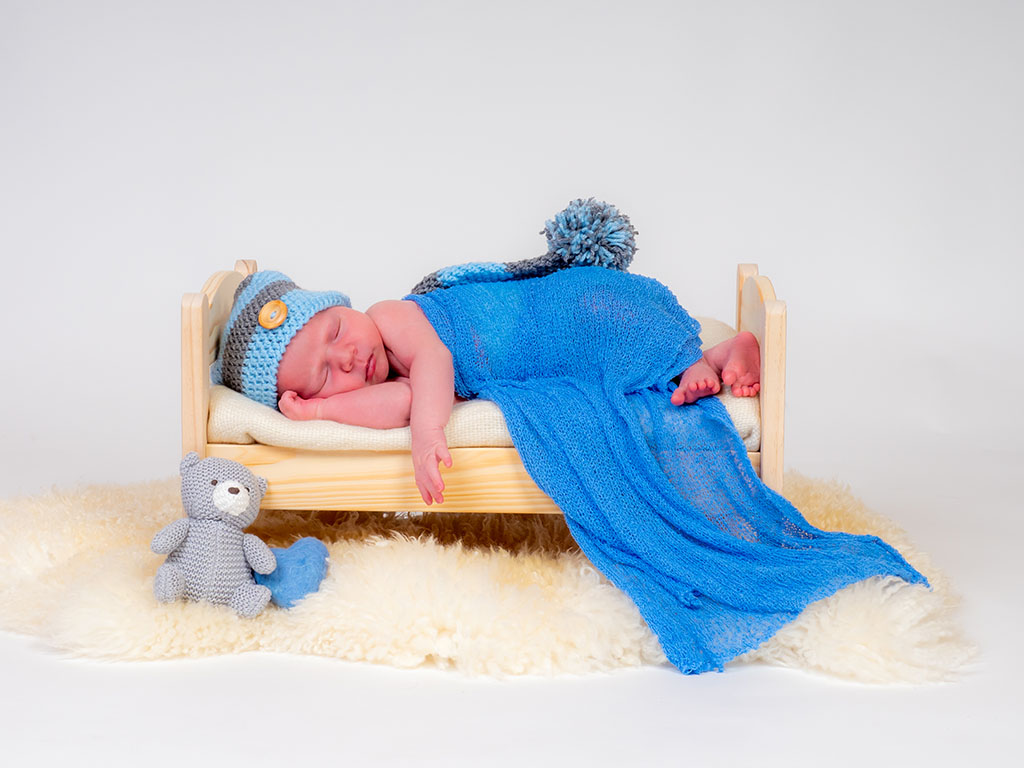 baby boy lying asleep on bed with knitted hat taken by newborn photographer in Braintree, Essex