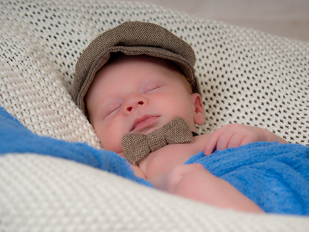 cute baby boy asleep wearing flap cap hat and matching bow tie taken by qualified newborn photographer in Braintree, Essex