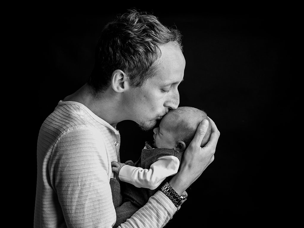 new father kissing newborn son baby boy taken by qualified newborn photographer in Braintree, Essex