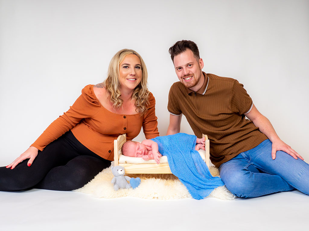 new parents with sleeping newborn baby on bed taken by qualified newborn photographer in Braintree, Essex