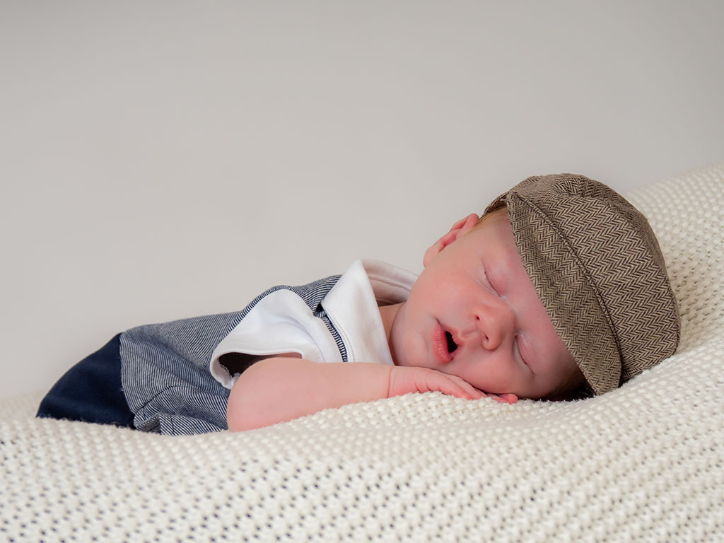 newborn baby asleep on soft beanbag with mouth open and wearing flap cap hat taken by qualified newborn photographer in Braintree, Essex