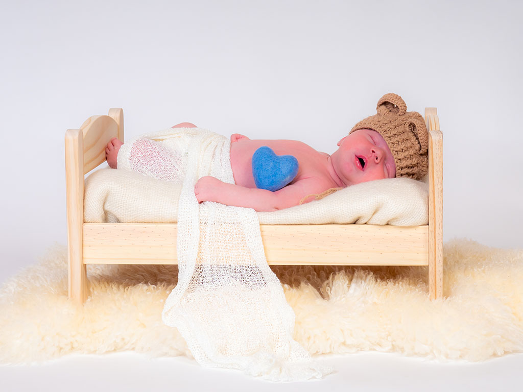 newborn baby fast asleep dreaming on bed with cosy wollen hat taken by qualified newborn photographer in Braintree, Essex