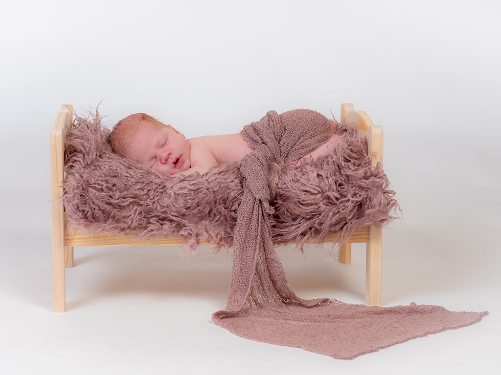 newborn baby girl fast asleep on bed dreaming with soft bedding and wrap drapped on flooring taken by qualified newborn photographer in Braintree, Essex
