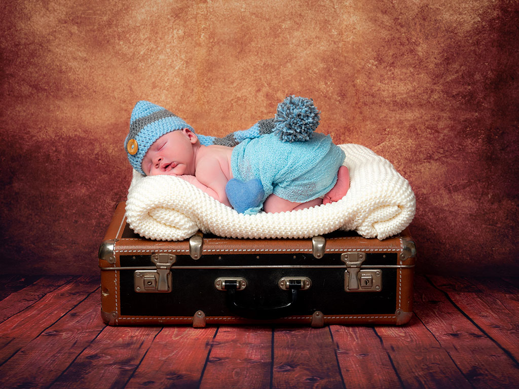 newborn baby sleeping on retro suitcase taken by qualified newborn photographer in Braintree, Essex